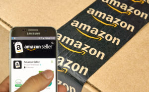 hand holding a cellphone while showing a box of amazon package