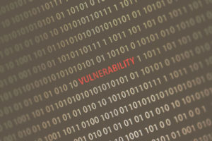 'Vulnerability' word in the middle of the computer screen surrounded by numbers zero and one.