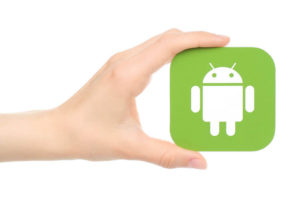 Hand holds Android logo printed on paper on white background.