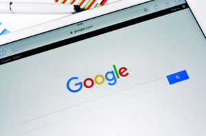 A tablet computer with the Google Web Search homepage in its screen with the new Google logo,
