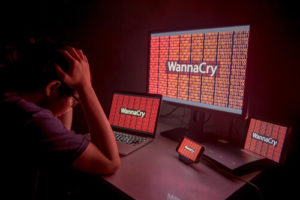 WannaCry ransomware attack on desktop screen, notebook and smartphone