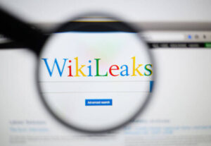 Photo of WikiLeaks homepage on a monitor screen through a magnifying glass