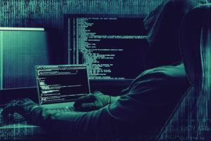 Internet attacker working on a code on dark digital background