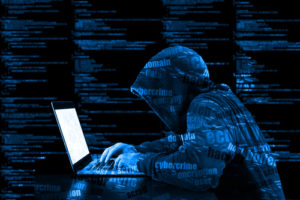 Hacker in a blue hoody standing in front of a code background with binary streams