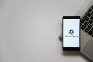 Wordpress logo on smartphone screen placed on laptop keyboard