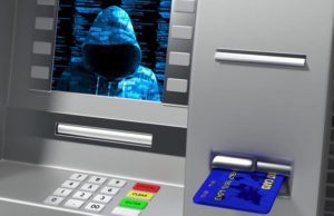 Hacked ATM while inserting credit card showing hoody hacker on the screen