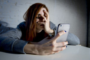 girl using mobile phone scared and desperate