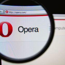 Photo of Opera homepage on a monitor screen through a magnifying glass.