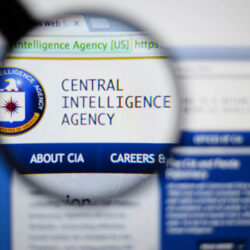 Photo of cia central intelligence agency. page on a monitor screen through a magnifying glass.