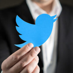 Close up of man in a suit showing printed Twitter logo.