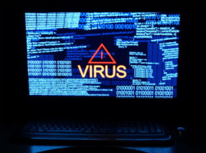 Computer in dark with word virus
