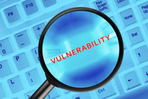 "Magnifying glass on computer keyboard with ""Vulnerability"" word."