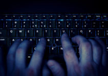 hands typing on keyboard in blue light with motion blur