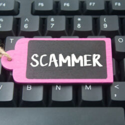 wooden tag written scammer over keyboard button background