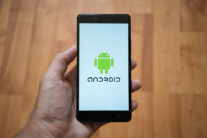 Man holding smartphone with Android logo on the screen. Laminate wood background.