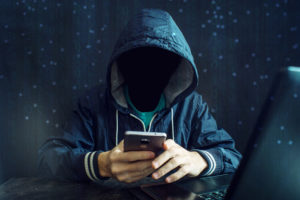 An anonymous hacker without a face uses a mobile phone to hack the system. Stealing personal data and money from Bank accounts. The concept of cyber crime and hacking electronic devices