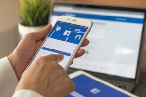Facebook social media app logo on log-in, sign-up registration page on mobile app screen on iPhone smart devices in business person's hand at work