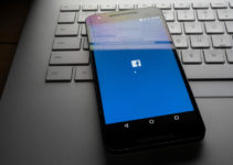 Facebook app on phone sitting on laptop with Facebook desktop site reflecting on screen.