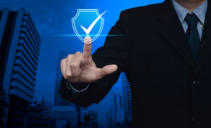 Businessman pressing security shield with check mark icon over modern office city tower and skyscraper.