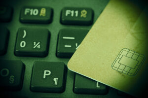 Golden credit card on black keyboard in dark environment with vignette
