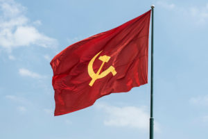 Large communist flag floating in the wind with a blue sky background