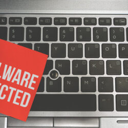 Concept Image of a red sticky note pasted on a keyboard with a message word white in color MALWARE DETECTED