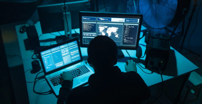 Wanted hackers coding virus ransomware using laptops and computers.