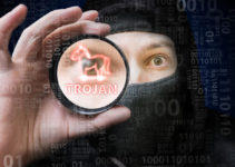 Masked anonymous hacker is cracking binary code with trojan malware.